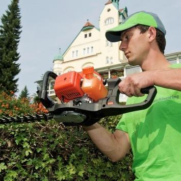 Mitarbeiter übernimmt das Hecken schneiden mit der Heckenschere im Rahmen der Maschinenring Grünraumpflege