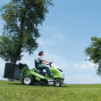 Rasen mähen - Maschinenring Mitarbeiterin auf Rasenmähertraktor übernimmt Gartenpflege