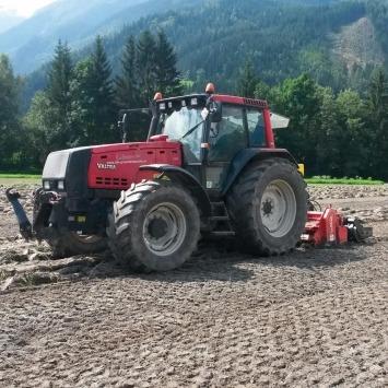 Rekultivierung nach Überschwemmungen, großen Bauprojekten etc. vom Maschinenring; im Bild Traktor der nach Überschwemmung Böden mit Umkehrfräse bearbeitet