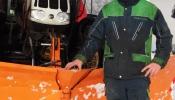 Mann vor einem Traktor mit Schneepfluge